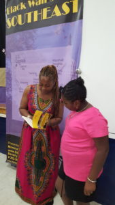 Author Beverly Smith signs a copy of her book, He Kept Me for a young admirer at her recent event, Black Wallstreet Southeast (June 2016)